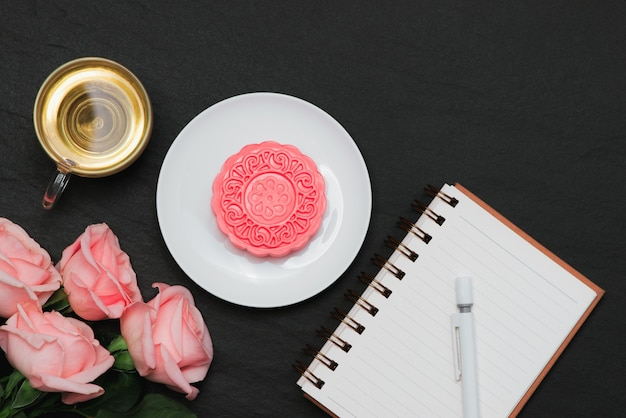 Mooncake de pele de neve e xícara de chá com flores. caderno aberto com cópia-espaço.