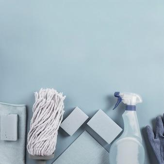 Mop cabeça, frasco de spray e esponja em fundo cinza