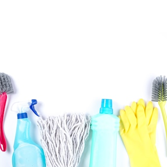 Mop cabeça, luvas, escova e garrafas de plástico no fundo branco