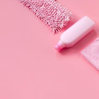 Mop, pano e detergente-rosa em fundo rosa para limpeza de primavera