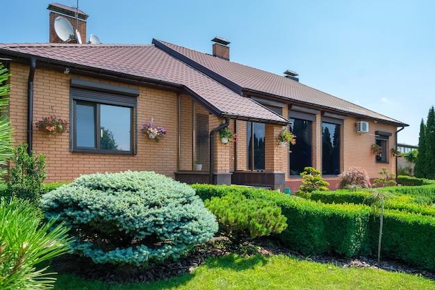 Moradia de estilo europeu com e jardim com arbustos bem aparados na frente da casa. projeto paisagístico. foto de alta qualidade