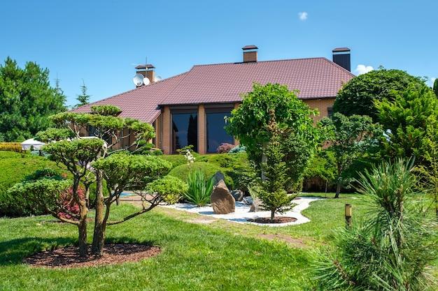 Moradia de estilo europeu com piscina e jardim com arbustos e árvores bem aparados na frente da casa. projeto paisagístico. foto de alta qualidade