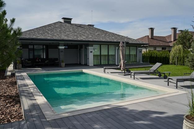 Moradia moderna com piscina e deck com interior. piscina em casa no jardim e terraço. verão, salão de praia, espreguiçadeiras no terraço para banhos de sol e piscina privada