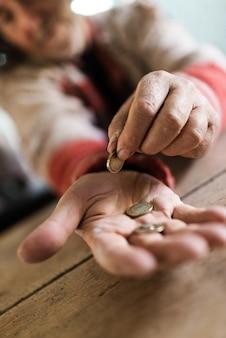 Morador de rua com suéter rasgado, contando as últimas moedas de euro. concentre-se na palma da mão com moedas.