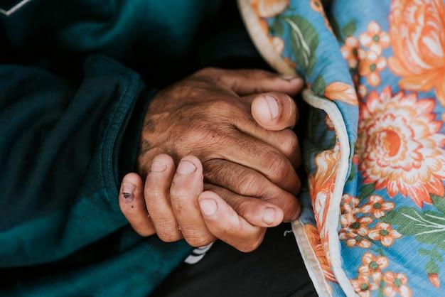 Morador de rua segurando suas mãos com cobertor