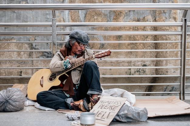 Morador de rua sujo sentado segurando um violão dormindo na ponte