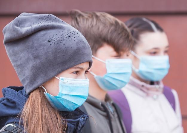 Moradores da cidade adultos e crianças que usam máscaras observam quarentena