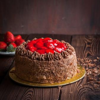 Morango, bolo de frutas de chocolate e morango fresco na mesa de madeira