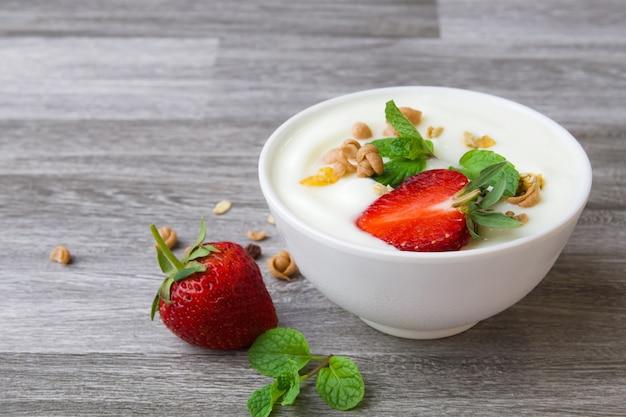 Morango com iogurte e hortelã na tigela sobre fundo de madeira