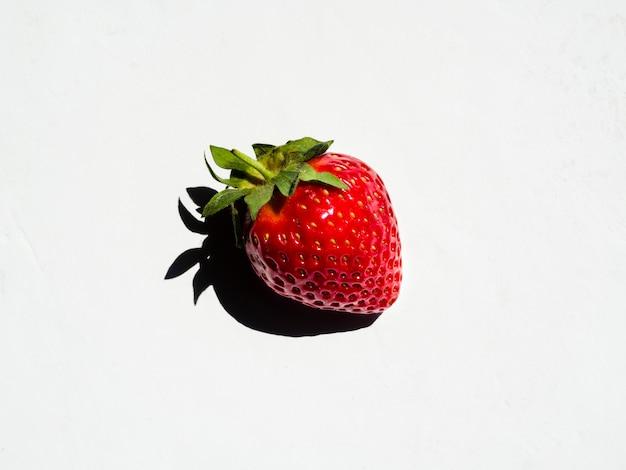 Morango doce fresca com sombra no fundo branco