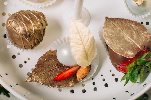 Morango e bombom decorado com folha de chocolate