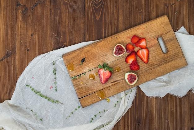Morango e figos em uma placa de madeira