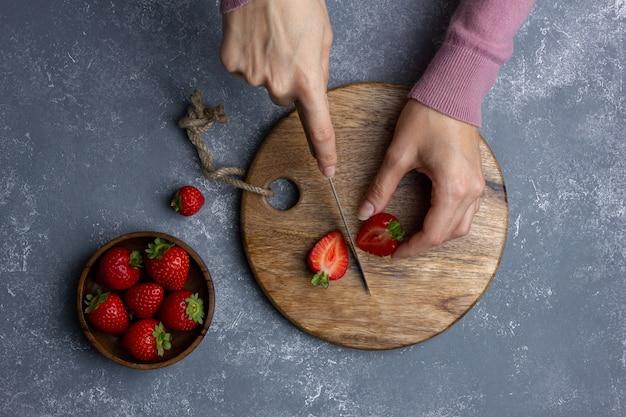 Morango em tigela de madeira. mãos femininas. vista superior de frutas frescas.