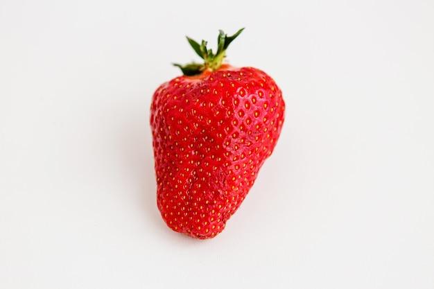 Morango em um fundo claro, fruta feia