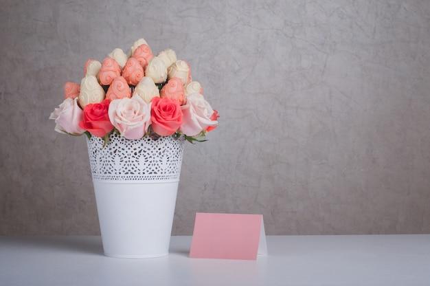 Morango fresco coberto por chocolate rosa e branco com flores rosas