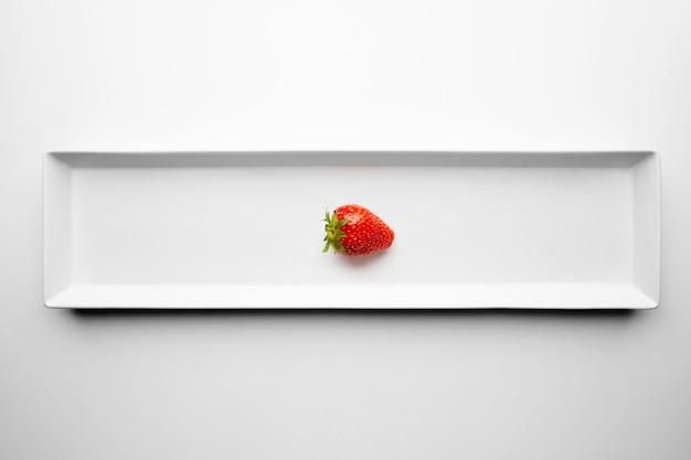 Morango maduro fresco e suculento isolado na placa cerâmica retangular no fundo da mesa branca. serviço de restaurante