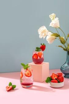 Morango mojito sobre fundo azul e rosa pódio. bebida refrescante de verão com espaço de cópia