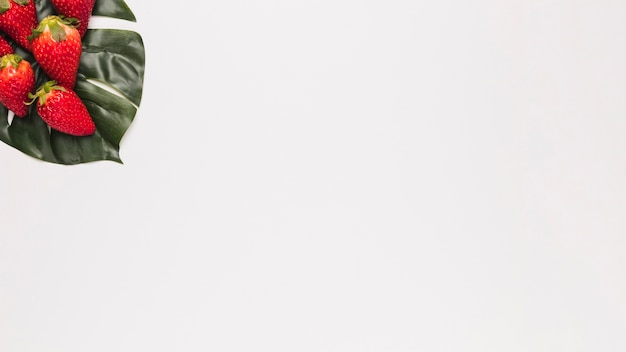 Morango vermelha na folha verde no canto da superfície branca