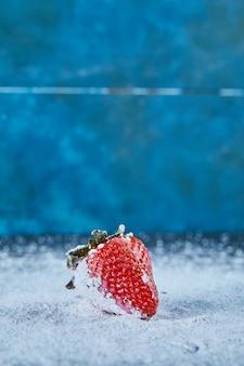 Morango vermelho fresco na superfície azul com pó