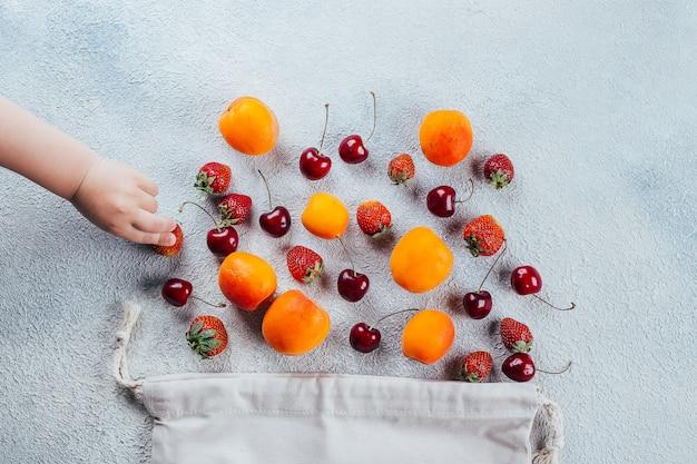 Morangos, cereja e damasco. a mão do bebê toma a baga