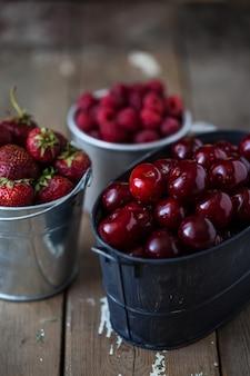Morangos, cerejas, framboesas em baldes em uma mesa de madeira