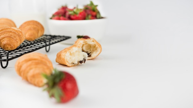 Morangos close-up com croissants em cima da mesa