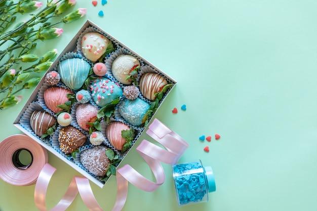 Morangos cobertos de chocolate artesanais, flores e decoração para cozinhar a sobremesa sobre fundo verde, com espaço livre para texto