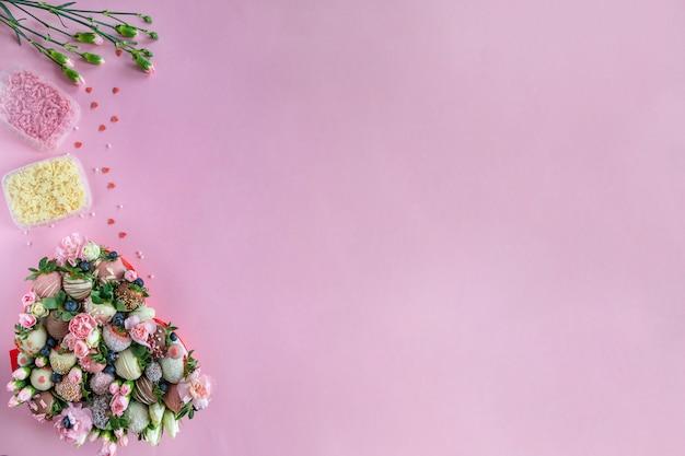 Morangos com cobertura artesanal de chocolate, flores e decoração para cozinhar a sobremesa em fundo rosa com espaço livre para texto