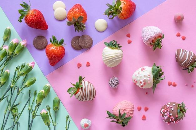 Morangos com cobertura em chocolate artesanais, flores e decoração para cozinhar a sobremesa em fundo colorido