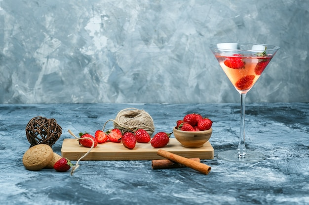 Morangos de close-up e uma faca na tábua com um copo de coquetel, clew, uma tigela de morangos e biscoitos em fundo de mármore azul e cinza escuro. espaço livre horizontal para o seu texto