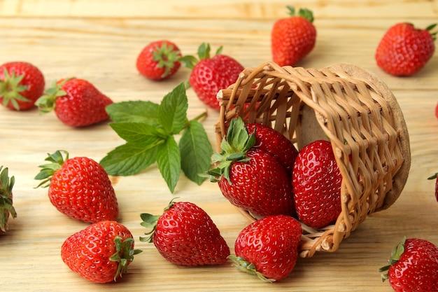 Morangos de frutas vermelhas em uma cesta de vime sobre uma mesa de madeira natural