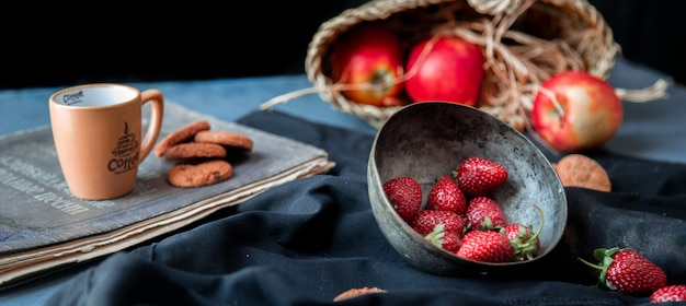 Morangos dentro da tigela, biscoitos, copo e maçã cesta em um tapete preto.