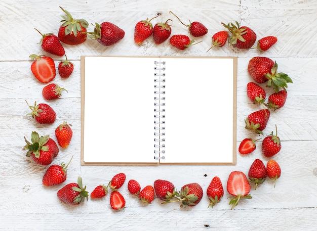 Morangos e caderno em uma mesa de madeira branca