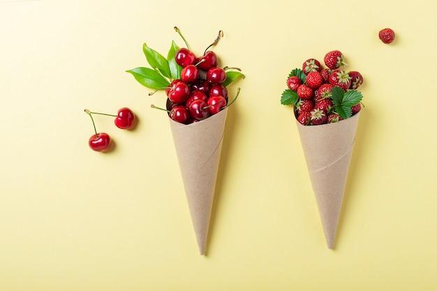 Morangos e cerejas em cones de papel