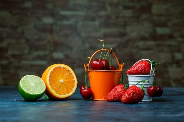 Morangos e cerejas em mini baldes com laranja, vista lateral para o limão na pedra de tijolo e fundo azul