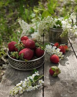 Morangos e flores de cerejeira na mesa antiga