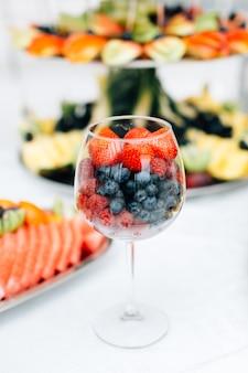 Morangos e mirtilos em um copo de vinho na mesa da restauração