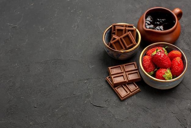 Morangos em close-up lateral em morangos de mesa em um prato de creme de chocolate em uma tigela e barras de chocolate no lado direito da mesa