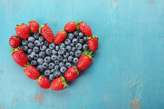 Morangos em forma de coração e mirtilos em madeira azul