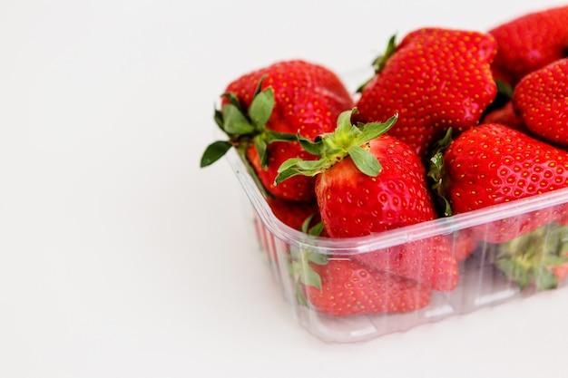 Morangos em um recipiente de plástico sobre um fundo claro, fruta feia