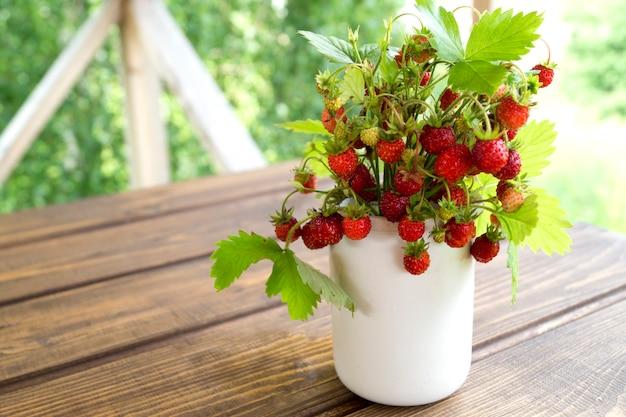 Morangos em uma caneca branca sobre uma mesa de madeira rústica. o conceito de comida orgânica. estilo rústico