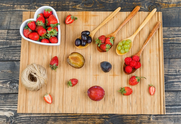 Morangos em uma tigela com frutas na colher de pau