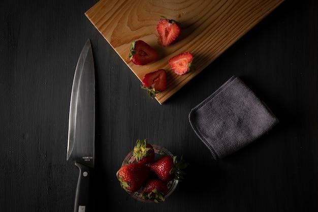 Morangos em uma tigela sobre uma mesa com uma tábua de cortar e uma faca ao lado
