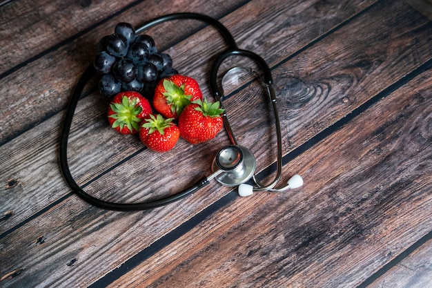Morangos escoceses vermelhos e uvas pretas com estetoscópio em cima da mesa de madeira. alimentos médicos e saudáveis conceituais.