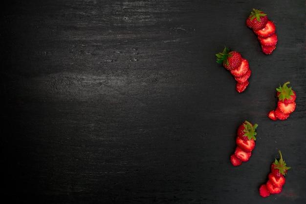Morangos fatiados com folhas em fundo preto. vista superior, moldura. copie o espaço. quadro de comida de frutas de verão.