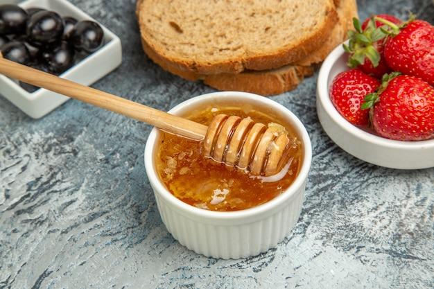 Morangos frescos com chá, pão e mel em comida doce de frutas no chão escuro.