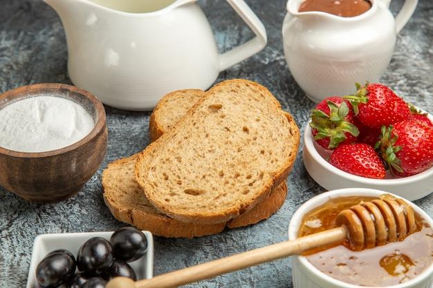 Morangos frescos com chá, pão e mel em comida doce de frutas superficiais escuras