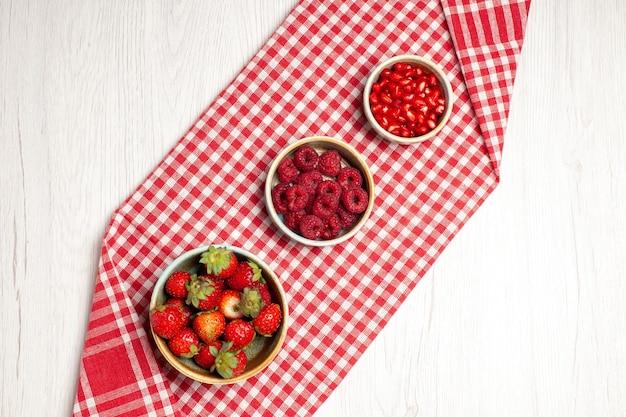 Morangos frescos com framboesas e romãs em uma mesa branca com frutas frescas frutas frescas maduras