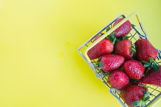 Morangos frescos com um carrinho de compras em um fundo amarelo brilhante. conceito de publicidade para produtos frescos. copie o espaço