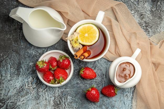 Morangos frescos com uma xícara de chá em frutas vermelhas superficiais claras e escuras